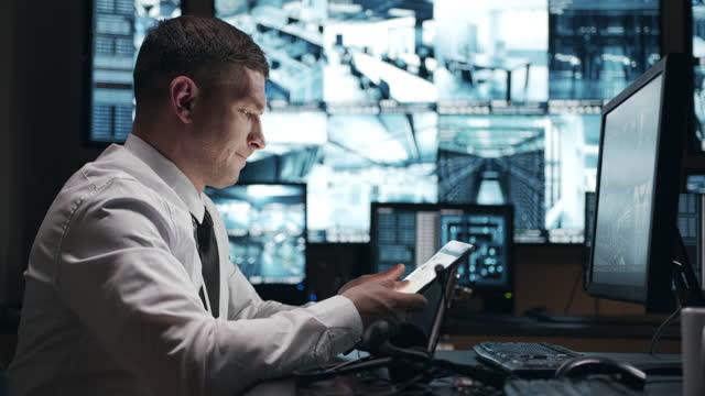 der notdienst-betreiber hat sich die betriebsübersicht auf einem tragbaren tablet angesehen. - militäruniform stock-videos und b-roll-filmmaterial