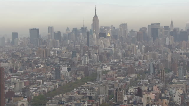 the empire state building towers over manhattan. - manhattan video stock e b–roll