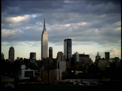 vídeos de stock, filmes e b-roll de the empire state building towers over the skyline of midtown manhattan. - ponto turístico internacional