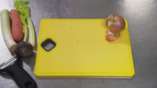 the ends of an onion are removed on a yellow chopping board - 余白点の映像素材/bロール