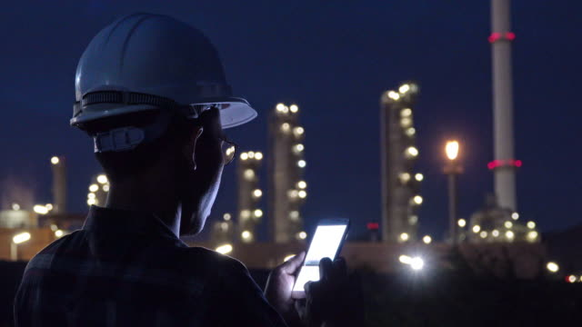 the engineer at industrial plant working on a smartphone. - mining natural resources stock videos & royalty-free footage