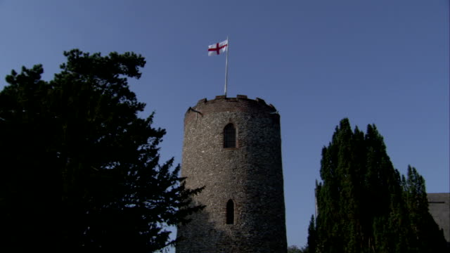 the english flag flies at the top of a round tower. available in hd. - bandiera inglese video stock e b–roll