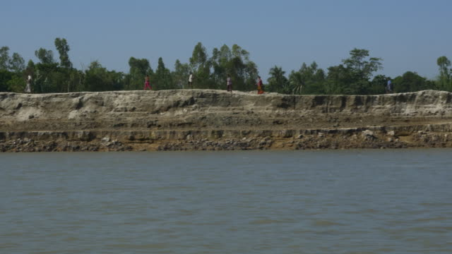 The eroded steep and fragile banks of the River Jamuna in Bangladesh filmed from a speed boat