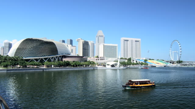 the esplanade and marina bay buildings with the singapore flyer ferris wheel and river sightseeing boat, singapore - ferry ride stock videos & royalty-free footage