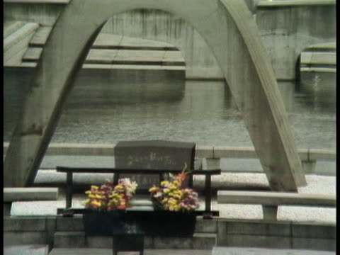 the eternal flame burns behind the memorial arch in the hiroshima peace park. - (war or terrorism or election or government or illness or news event or speech or politics or politician or conflict or military or extreme weather or business or economy) and not usa点の映像素材/bロール