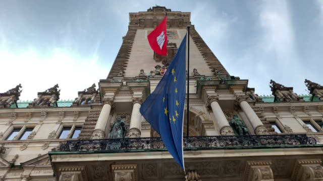 the european union flag in front of the hamburg town hall (rathaus), the seat of the state parliament - rathaus hamburg stock-videos und b-roll-filmmaterial