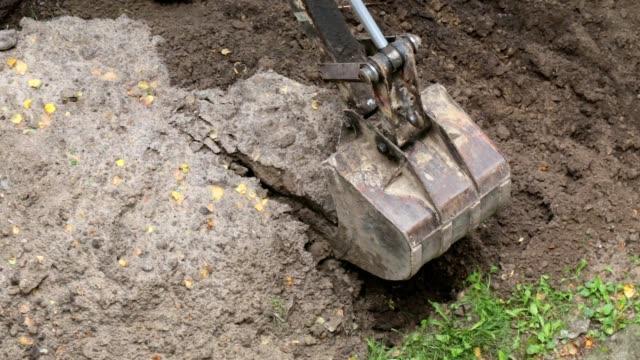 vídeos y material grabado en eventos de stock de cubo del excavador mueve el suelo. - cucharón