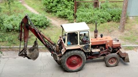 vídeos y material grabado en eventos de stock de la excavadora se mueve hacia atrás a lo largo de la carretera. - cucharón