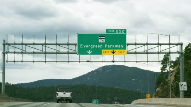"the ""exit 252: evergreen parkway (colorado highway 74)"" exit sign from a vehicle's perspective driving westbound on interstate 70 in the rocky mountains of colorado on a partly cloudy day - segnaletica stradale video stock e b–roll"