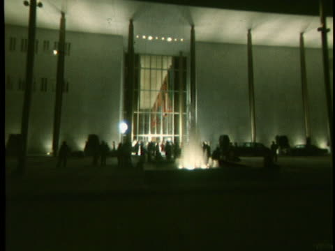 ls of the exterior of the kennedy center on its opening night of september 8 1971 a fountain is seen as is a window that shows various flags inside... - performing arts center stock videos & royalty-free footage