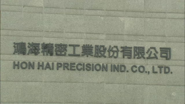 The exterior view of the headquarters of Foxconn Zooming out of the company logo on the front entrance Wide angle view of the building façade