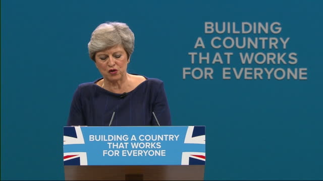 the 'f' from the conservative party slogan 'building a country that works for everyone' falling off during theresa may's speech at the party... - theresa may stock videos & royalty-free footage