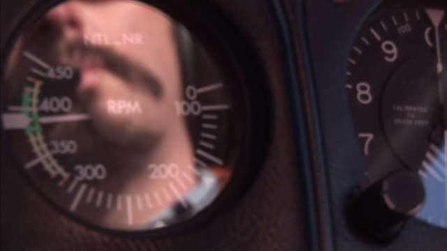 the face of a pilot reflects on a cockpit instrument panel gauge. - 計測器点の映像素材/bロール