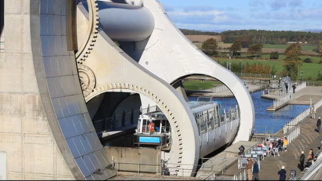 the falkirk wheel at falkirk in scotland uk. it is a unique rotating boat lift connecting the forth and clyde canals. the difference in levels of the two canals at the wheel is 79 feet, or 24 metres - fluss firth of forth stock-videos und b-roll-filmmaterial