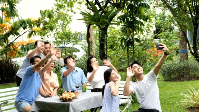 家族や多くの世代が庭で一緒に写真を撮る - 大人数点の映像素材/bロール