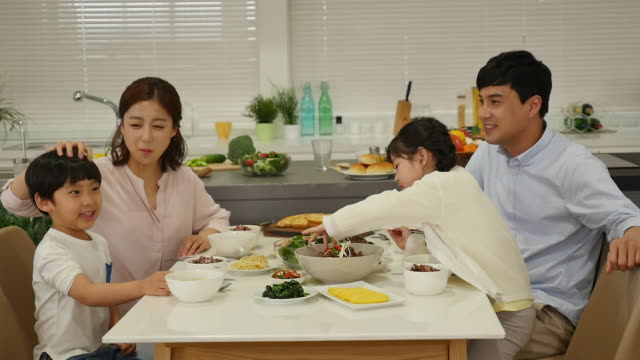 the family eat a meal sitting on the table - 東洋民族点の映像素材/bロール