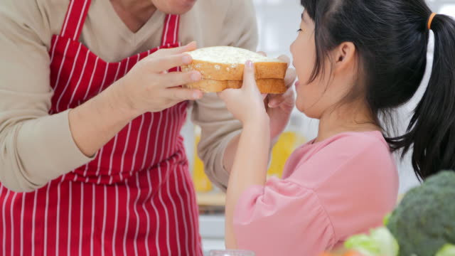 the family is happy with the father and the girl eating the bread in the kitchen together.japanese families - baby girls stock videos & royalty-free footage
