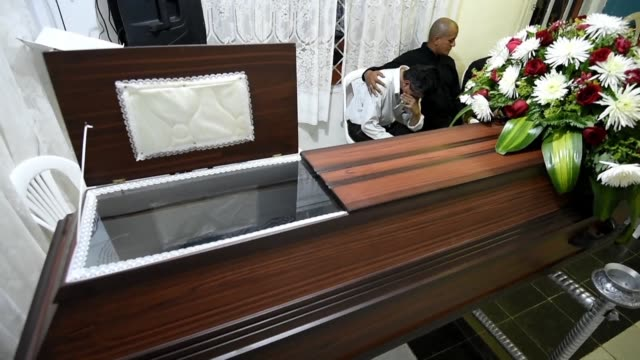 the family of a 20 year old venezuelan migrant who was murdered in the colombian city of cali sit around his coffin for the ninth day as they wait... - resurrection religion stock videos & royalty-free footage