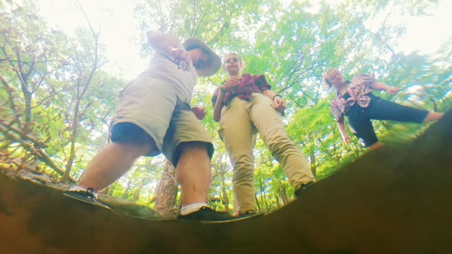 the family of tourists-hikers, the mature man, and two teenage girls, washing hands in the brook's flow and refreshing after a walk. looking upward from the flow 's bottom through the water surface. - upside down stock videos & royalty-free footage