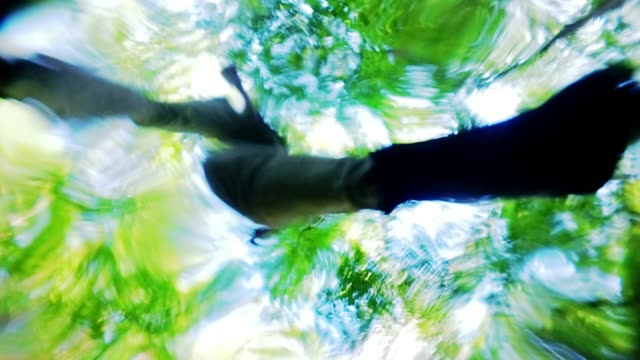 the family of tourists-hikers, two teenage girls and the mature man, father, jumping over the brook in the forest one after another. unusual point of view upside-down, looking upward from the bottom of the flow through the water surface. - looking through an object stock videos & royalty-free footage