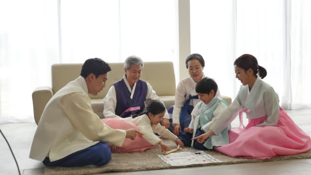 vídeos de stock e filmes b-roll de the family play a game of yut (korean traditional board game) on new year's day - korean new year