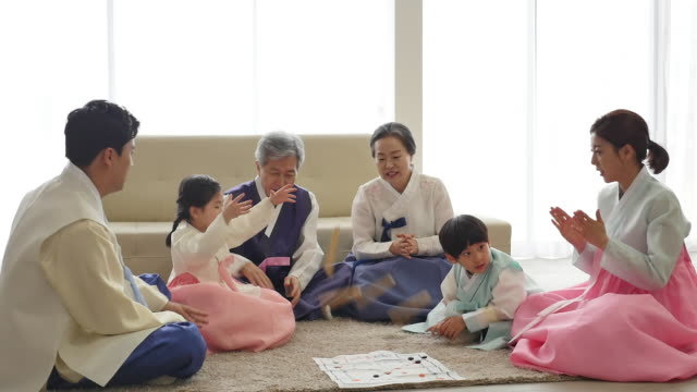 stockvideo's en b-roll-footage met the family play a game of yut (korean traditional board game) on new year's day - traditie