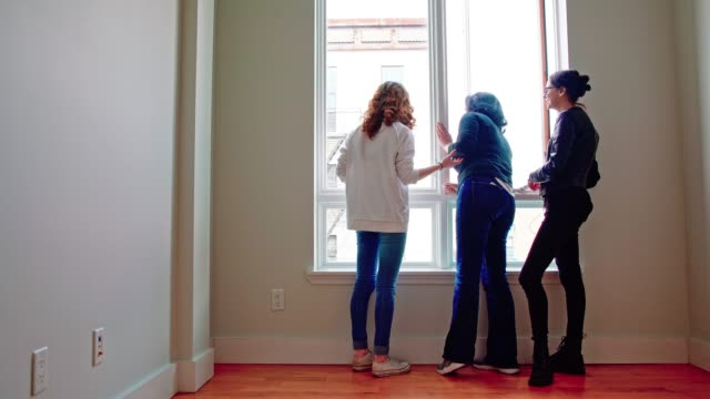 the family, the mother and two teenager daughters, exploring the new apartment. looking on the window in the empty room. - 18 19 years stock videos and b-roll footage