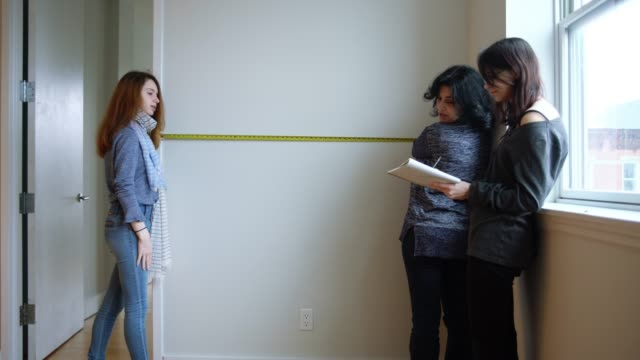 the family, the mother, and two teenager daughters measures the empty room in the new apartment to planning furniture placement. - 18 19 years stock videos and b-roll footage