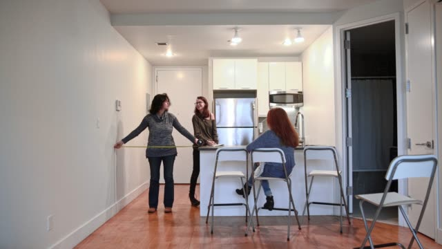 the family, the mother, and two teenager daughters measures the empty room in the new apartment to planning furniture placement. - measuring stock videos & royalty-free footage
