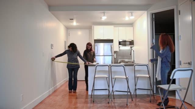 La famille, la mère et deux mesures de filles d'adolescent le vide chambre dans l'appartement neuf à planifier l'emplacement des meubles.