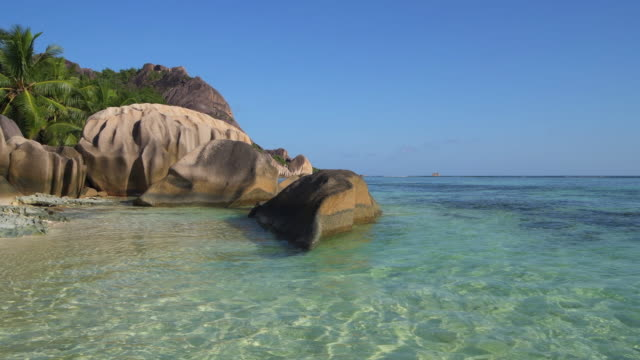 the famous tropical beach anse source d´argent with white sand and boulder rock formations and crystal clear water. - naturwunder stock-videos und b-roll-filmmaterial