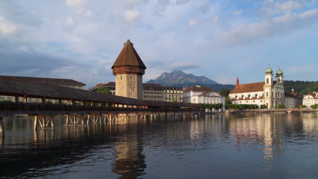 the famous wooden footbridge kapellbrücke spanning across the reuss river with the jesuit church in background, in the city of lucerne. lucerne, lucerne canton, switzerland. - überdachte brücke brücke stock-videos und b-roll-filmmaterial
