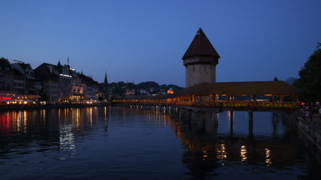 the famous wooden footbridge kapellbrücke spanning across the reuss river, in the city of lucerne illuminated at night. lucerne, lucerne canton, switzerland. - uferviertel stock-videos und b-roll-filmmaterial