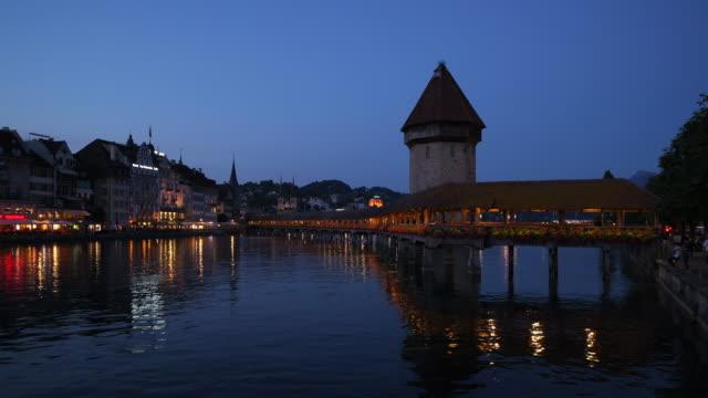 vídeos de stock, filmes e b-roll de the famous wooden footbridge kapellbrücke spanning across the reuss river, in the city of lucerne illuminated at night. lucerne, lucerne canton, switzerland. - frente ao mar