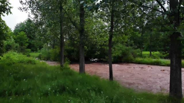 vídeos y material grabado en eventos de stock de el río rápido fluye a través del pueblo y lleva todo en frente de él - un río rápido fangoso - fuertes lluvias - desastre natural - multicóptero