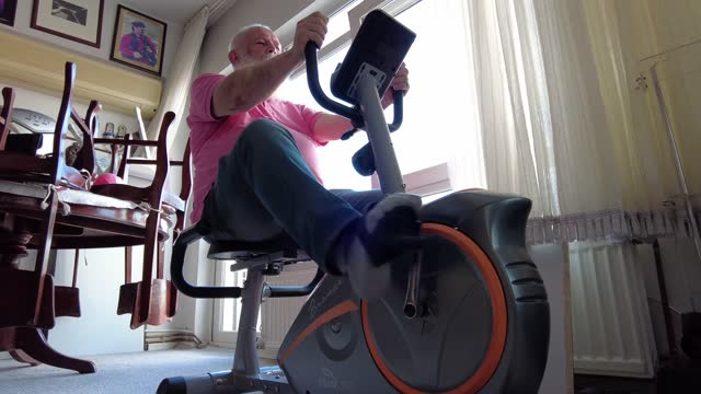 the fat senior man, who could not go out of his house during the pandemic process, bought a home sports bike and is trying to do sports at home on... - active seniors stock videos & royalty-free footage
