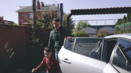 The father and son getting out of the car. slow motion