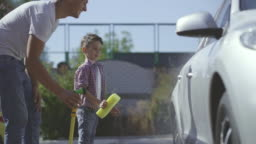 The father and son washing a car with hosepipe and sponge. slow motion