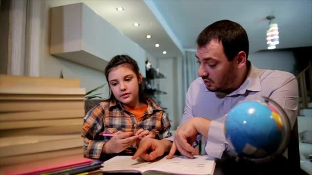 vídeos y material grabado en eventos de stock de el padre ayuda a su hija hacer los deberes. padre ayuda a su hijo - deberes