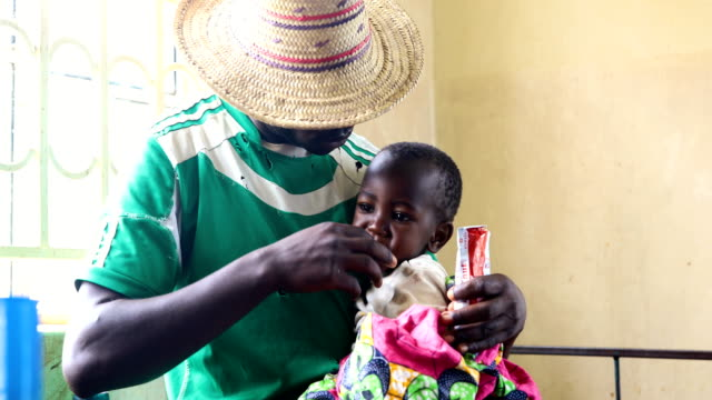 The father of a oneyearold refugee from the Democratic Republic of Congo with severe malnutrition feeds her readytouse therapeutic food in a ward at...