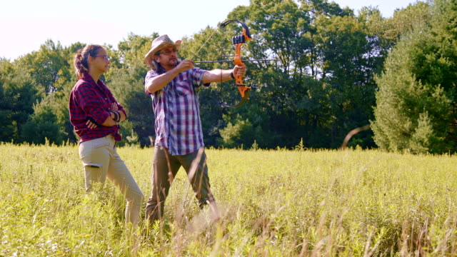 the father teaches his daughter, the teenager girl, to shoot a bow - archery bow stock videos and b-roll footage