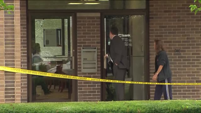 the fbi is looking for the 3 men who robbed a us bank at gun point investigators enter bank after robbery on august 22 2013 in lansing illinois - lansing stock-videos und b-roll-filmmaterial