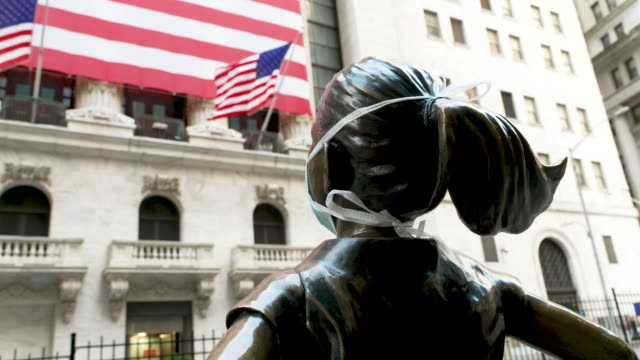 the fearless girl statue stands looking at the new york stock exchange wearing a face mask the sculpture stands on wall street amid the outbreak of... - mercato luogo per il commercio video stock e b–roll