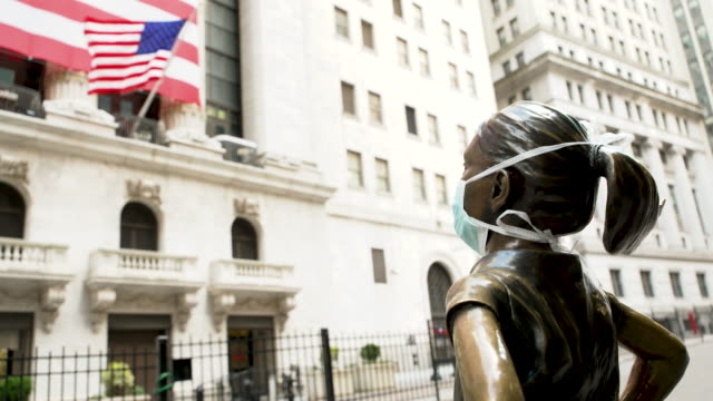 vídeos y material grabado en eventos de stock de the fearless girl statue stands looking at the new york stock exchange wearing a face mask. the sculpture stands on wall street amid the outbreak of... - wall street