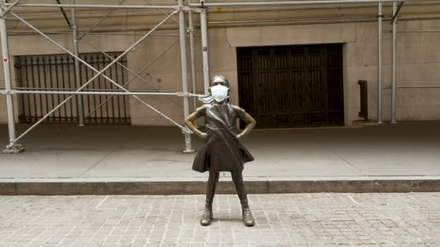 the fearless girl statue stands looking at the new york stock exchange wearing a face mask. the sculpture stands on wall street amid the outbreak of... - downtown stock videos & royalty-free footage