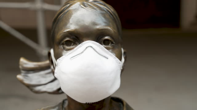 the fearless girl statue stands looking at the new york stock exchange wearing a face mask. the sculpture stands on wall street amid the outbreak of... - manhattan stock videos & royalty-free footage