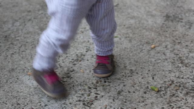 the feet of a baby girl and a group of people dancing outside together. - endast flickor bildbanksvideor och videomaterial från bakom kulisserna