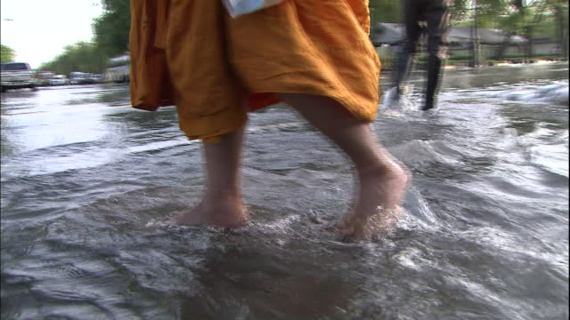The feet of a Buddhist priest wade through flood water in a Bangkok street