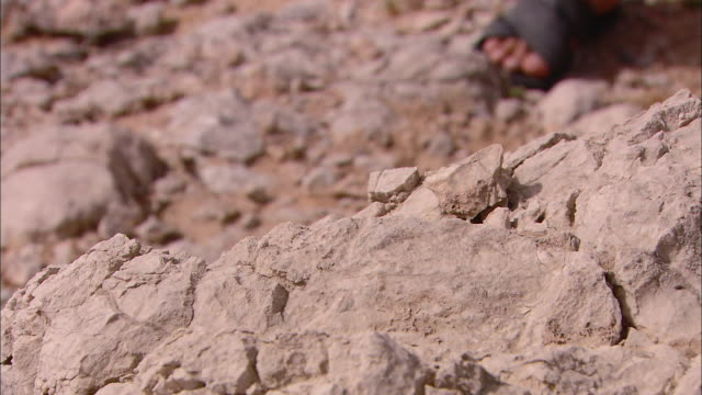 the feet of a saudi dressed in white robes climbs over desert rocks. - land stock videos & royalty-free footage