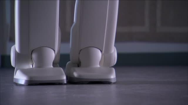 the feet of asimo, a humanoid robot, take a few steps backward then forward. - asimo stock videos & royalty-free footage